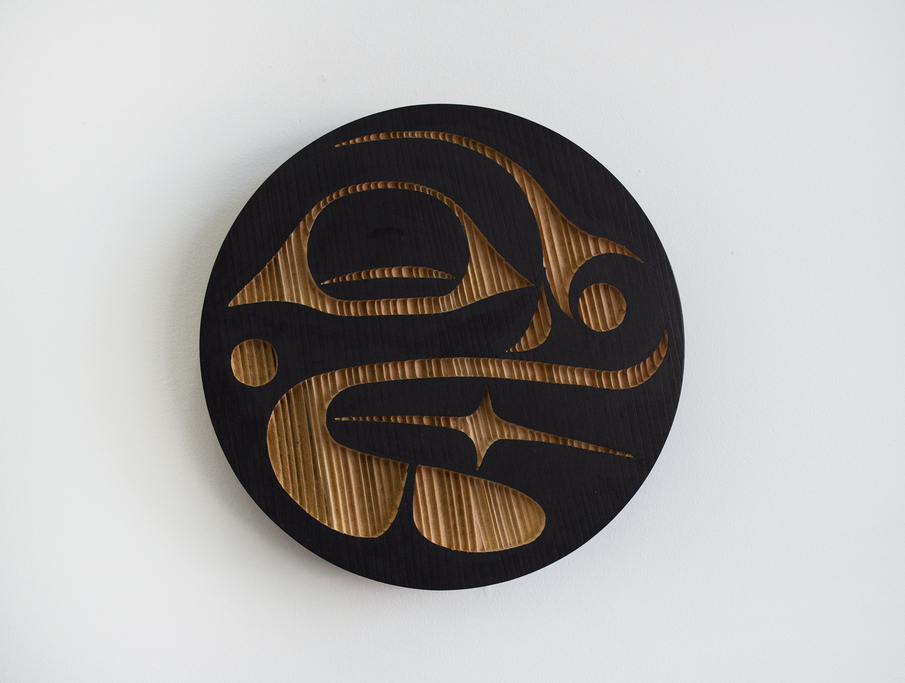 "Bear Panel 2, 2018, Jazmine Mccrimmon-Cook (Kwakwaka'wakw), Sandblasted and painted red cedar, 12"" diameter x 2"" depth, $400"
