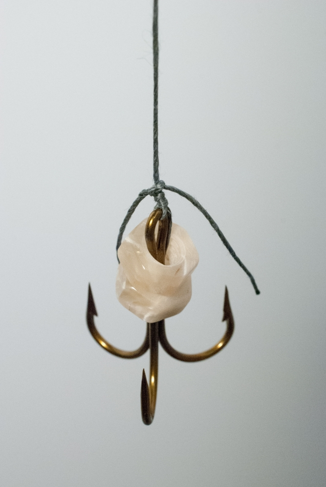 "Fishing Weights (2015), Couzyn van Heuvelen (Inuk), Muskox horn, fish hook, thread, brass, 6"" x 1"" x 48"", $700"
