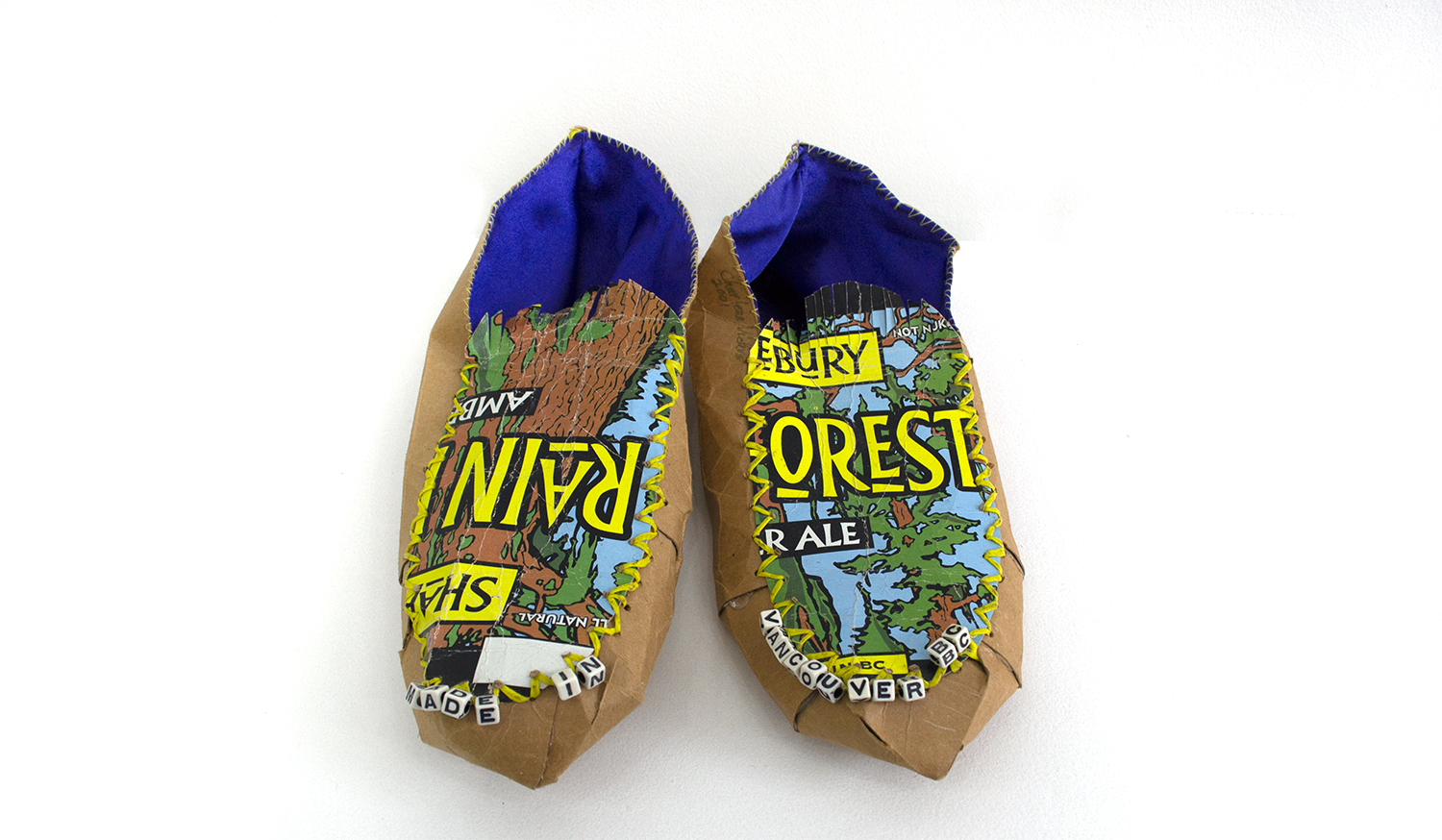 "Rainforest Ale Made in Vancouver Moccasin, 2001, Charlene Vickers (Anishnabe), Beer box paper, synthetic lacing, fabric, letter beads, 12"" x 9.5"" x 4"", SOLD"