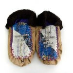 "The Customer is Always Right Moccasin, 2001, Charlene Vickers (Anishnabe), Beer box paper, faux fur, thread, fabric, letter beads, 11"" x 10"" x 3"", SOLD"