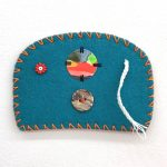 "Ovoid Felts, Charlene Vickers (Anishnabe), Watercolour, paper, shell buttons, glass beads on felt with embroidery edges, 5"" x 3.5"", SOLD"